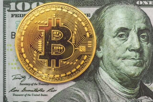 A bitcoin and a one hundred dollar bill.