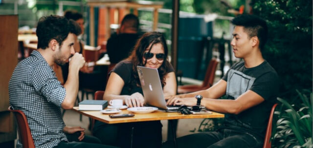 Two men and a woman sit outside at a cafe and work on a laptop.