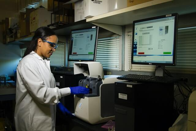 A doctor works in a laboratory near computers and medical equipment.