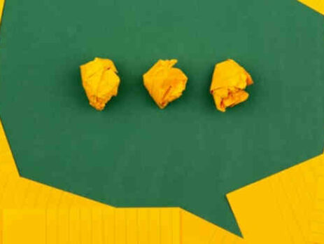 Three pieces of crumpled up yellow paper on a green background