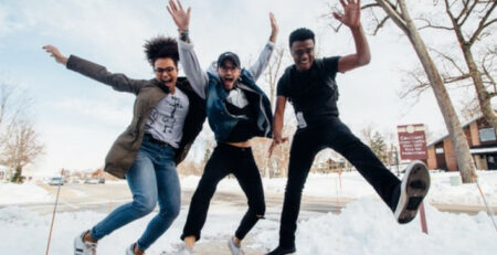 Three people jump in the air in a snowy field.