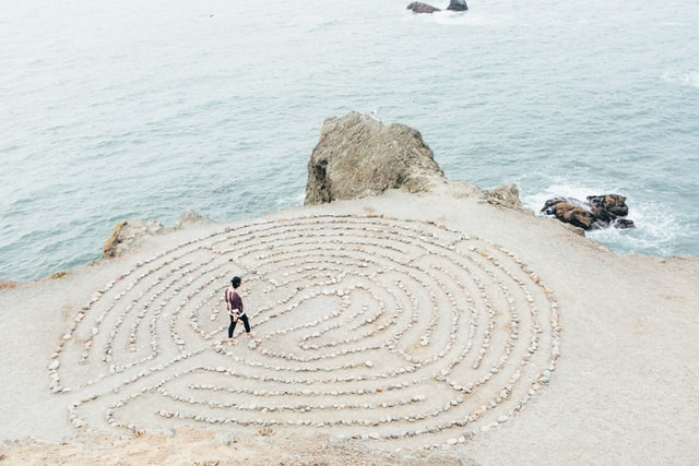 A person enters a rock maze on the beach.
