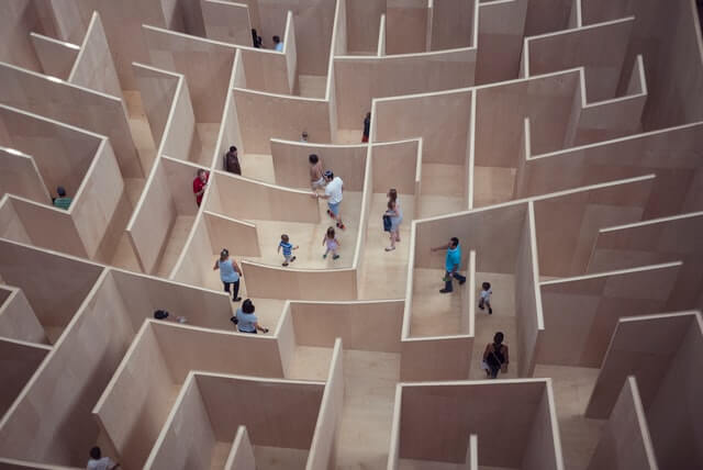 People and families walk around a maze.