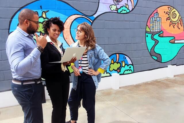 Three people talk around a computer in front of graffiti.