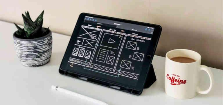 An iPad next to a coffee mug on a white desk.