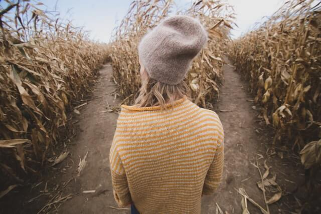 A woman in a yellow sweater and hat stands near two roads.