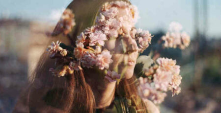 A double exposure of a woman and some flowers.