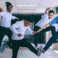 Business people jumping in the air in a hallway.