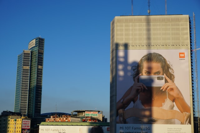 A cityscape and a billboard featuring a woman with a phone.