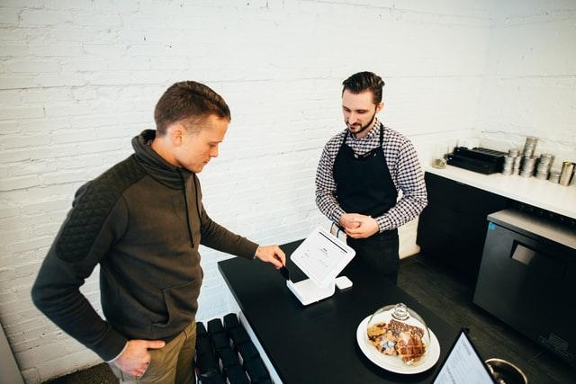 Two men speak over a small white cash register.