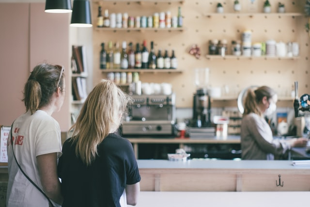 Two women wait for a barista in a coffee shop.