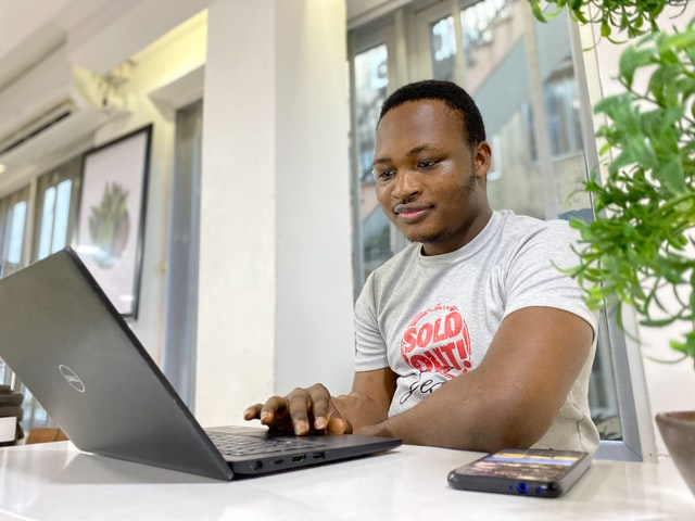 A man sits at a white table and works on a laptop computer.