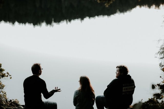 Three people sit near a lake and talk.