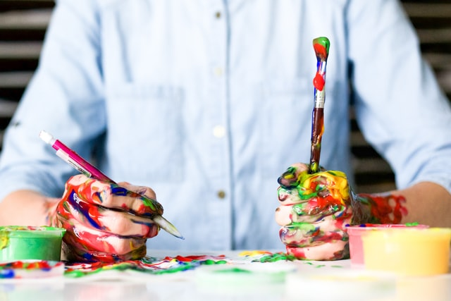 Someone holding paintbrushes covered in paint.
