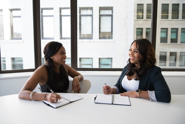 Two women sit at a conference table laughing and talking.