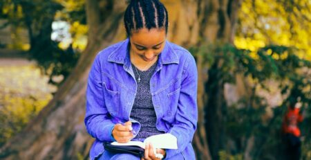 A person reading a book while sitting underneath a tree.