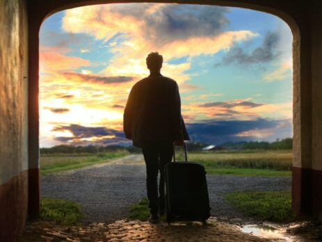 A man with a suitcase walking through a doorway outside.