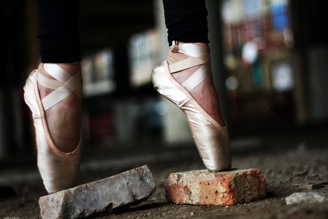 Two feet in ballerina slippers poised on platforms.